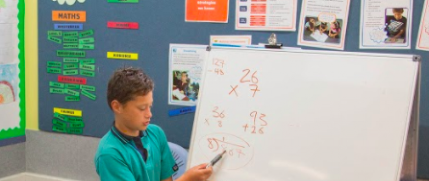 Student working out a maths problem on the whiteboard.